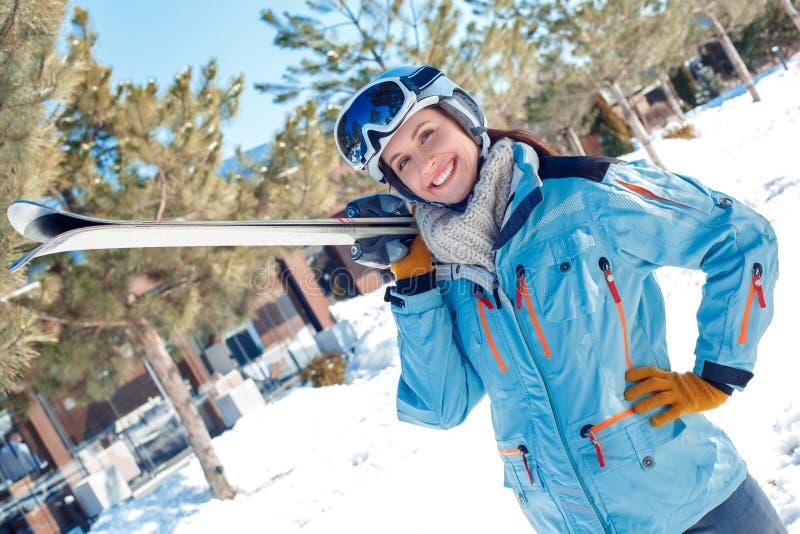 Férias do inverno Mulher nos óculos de proteção e capacete que está fora com os esquis que levantam à câmera alegre fotografia de stock