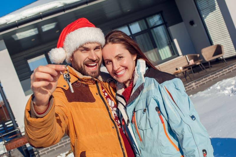 Férias do inverno Posição nova dos pares junto fora com chaves do close-up entusiasmado de sorriso do apartamento novo imagens de stock