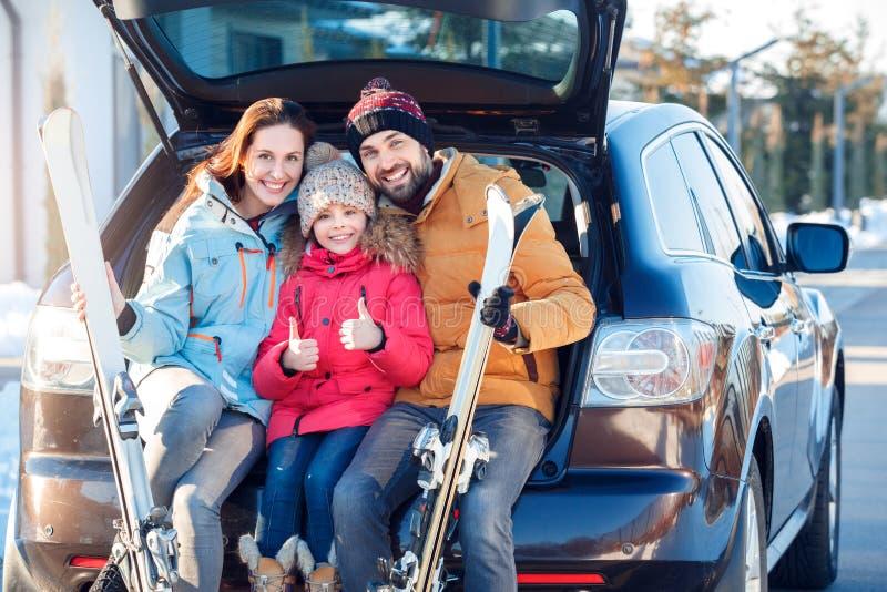 Férias do inverno Tempo da família junto que está fora o aperto de assento no tronco de carro com a menina alegre de sorriso dos  fotos de stock
