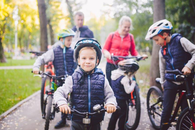 Férias dos esportes da família do tema no parque na natureza família caucasiano amigável grande de seis pessoas do Mountain bike  imagem de stock