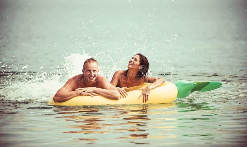 Férias e curso de verão ao oceano Pares no sunbath do amor na praia no colchão de ar Colchão inflável do abacaxi fotos de stock royalty free