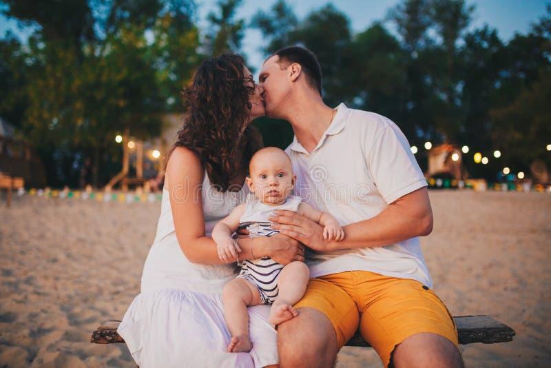 Férias em família do tema no verão perto do rio beijo do homem e da mulher, um filho pequeno da criança que senta-se em suas mãos imagem de stock