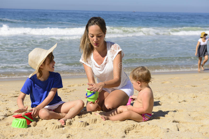 Férias em família na praia: Mãe e crianças fotografia de stock royalty free