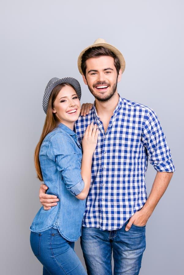 Férias junto Pares novos felizes no vestuário desportivo e nos chapéus AR fotos de stock