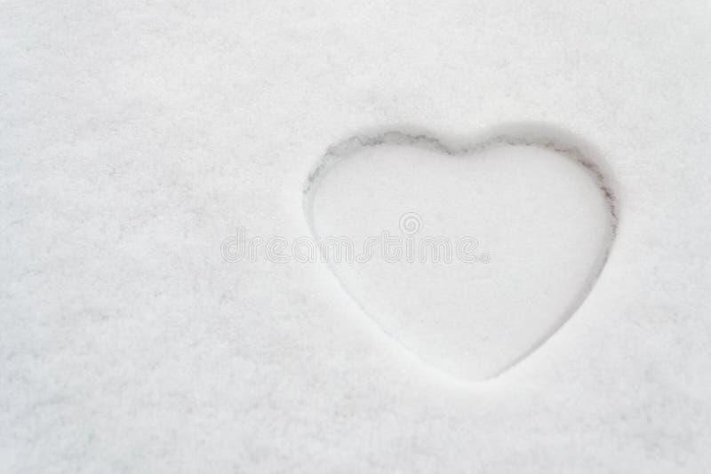 14 février concept, thème de fête des mères ou de jour de femmes : Grand contour blanc d'un coeur dans la neige photo stock