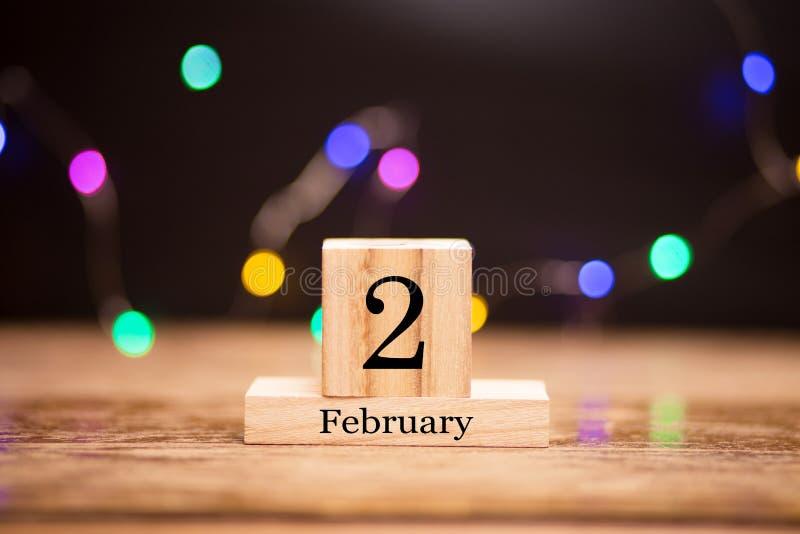 2 février Jour 2 d'ensemble de mois de février sur le calendrier en bois au centre du fond foncé avec le bokeh de guirlande Horai photographie stock libre de droits