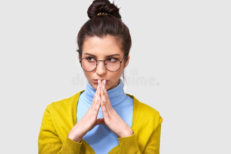 A fêmea à moda, compõe o plano, mantém as palmas junto, olhando de lado, veste a camiseta amarela e a blusa azul, eyewea redondo fotografia de stock