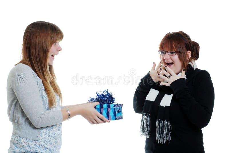 Fêmea adolescente que dá a sua irmã um presente imagem de stock royalty free