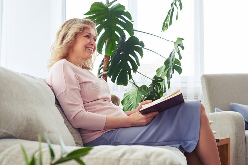 Fêmea adulta bonita que sorri quando livro de leitura fotos de stock