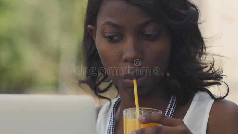 Fêmea afro-americana bonita na roupa ocasional que aprecia o tempo livre que senta-se na tabela no café usando o portátil e beber fotografia de stock