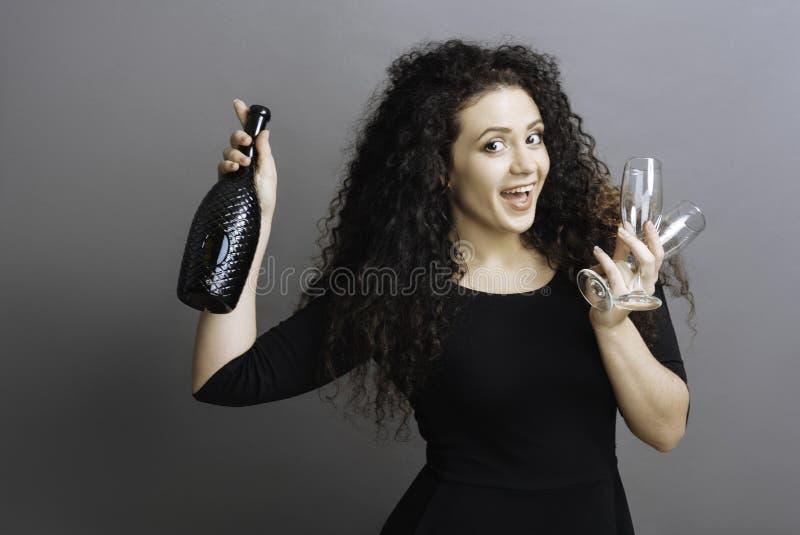 Fêmea alegre que guarda a garrafa preta imagens de stock royalty free