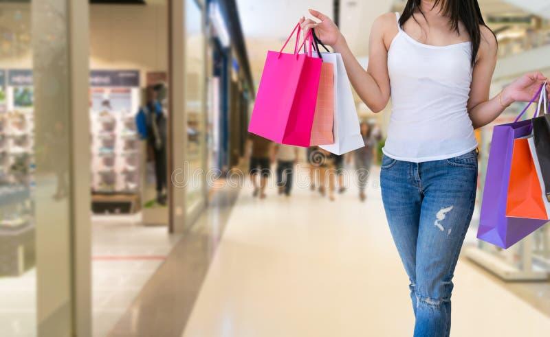 A fêmea anda as mãos que guardam sacos de compras da venda na alameda fotos de stock