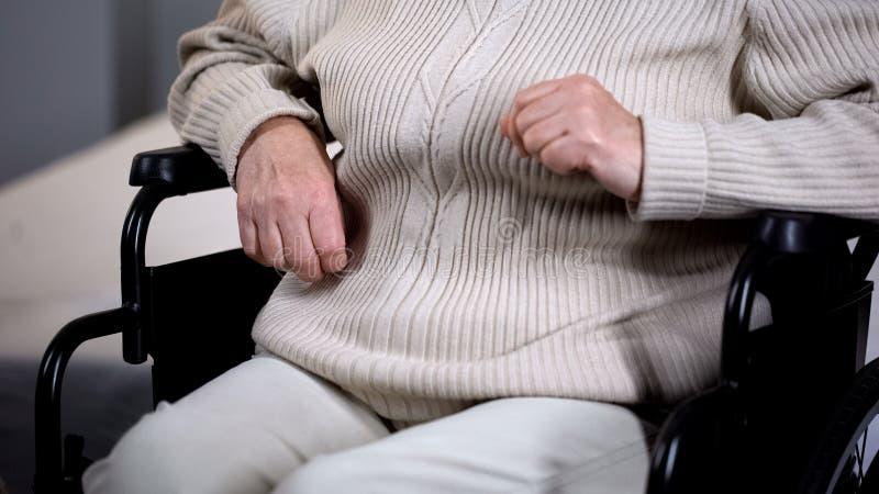 A fêmea aposentou-se o close up de assento da cadeira de rodas da senhora, inabilidade da idade avançada, lar de idosos imagens de stock