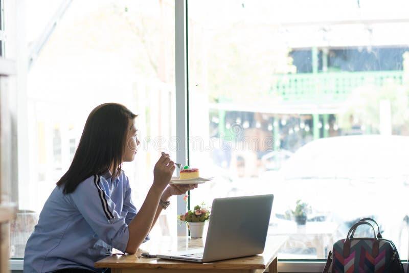 fêmea asiática atrativa que aprecia sua fatia de morango apenas dentro do café com portátil imagem de stock royalty free