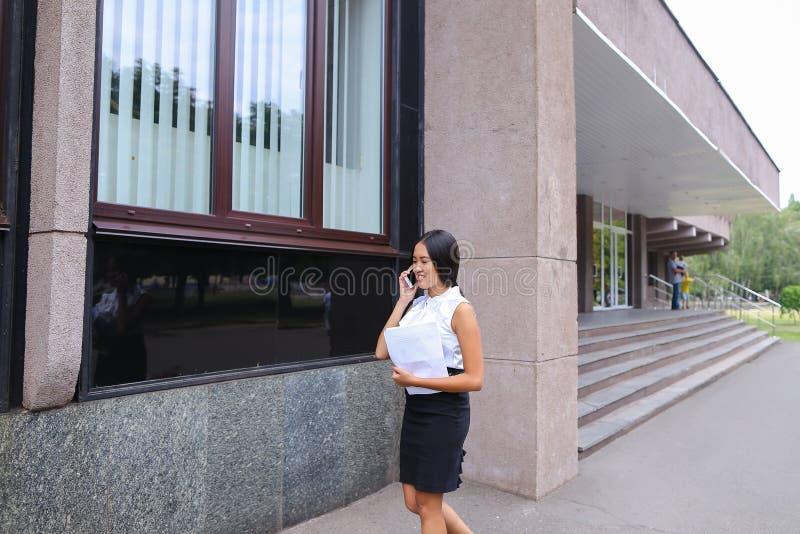 A fêmea asiática do negócio novo anda e fala no telefone, guarda o docu imagens de stock royalty free