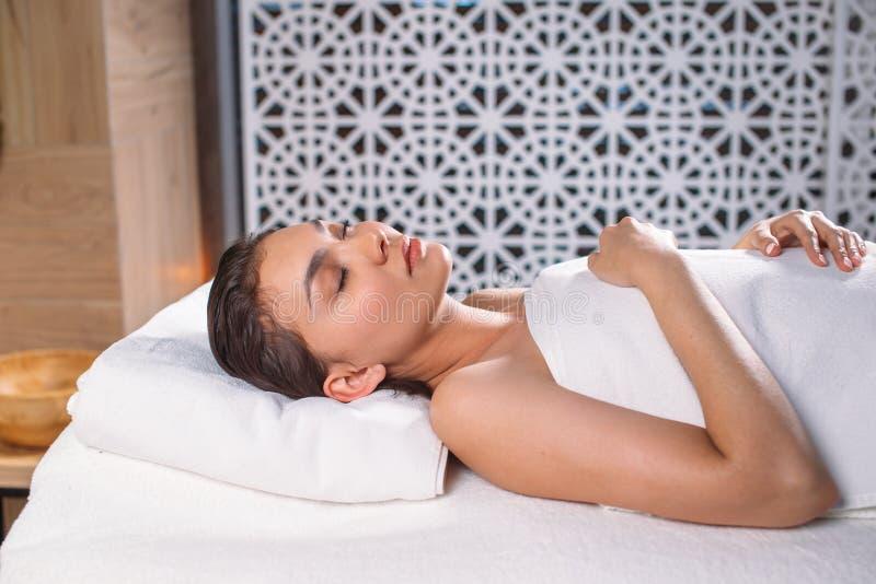 Fêmea asiática nova com os olhos fechados que descansam na tabela da massagem fotos de stock