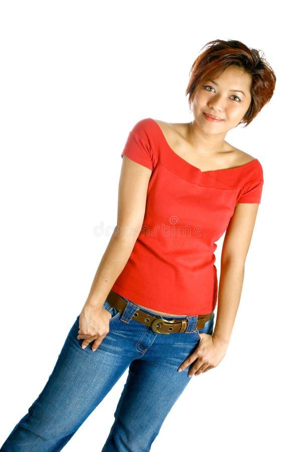 Fêmea asiática nova na parte superior e no je ocasionais vermelhos brilhantes foto de stock royalty free
