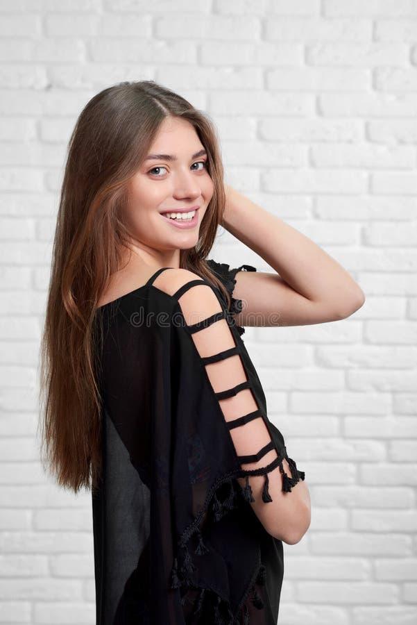 Fêmea atrativa de sorriso no pareo escuro na frente da parede de tijolo branca imagem de stock