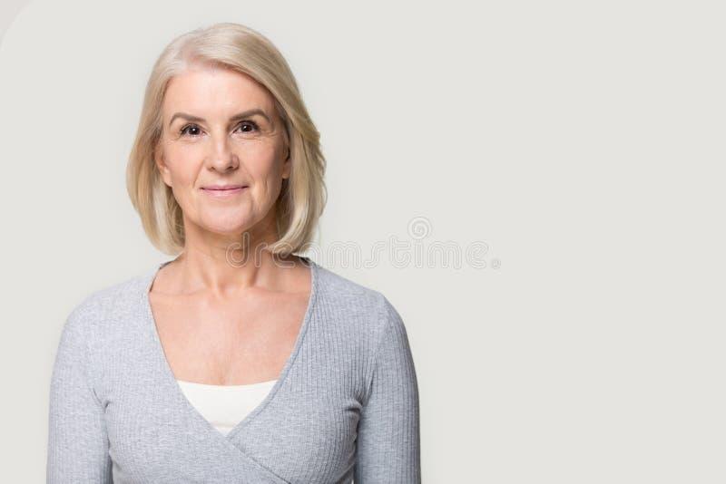 Fêmea atrativa madura do retrato do Headshot isolada no fundo cinzento do estúdio fotos de stock