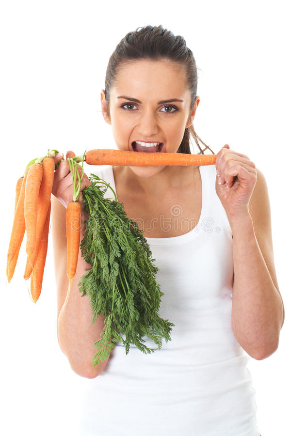 A fêmea atrativa nova come as cenouras, isoladas foto de stock