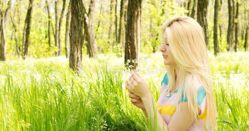 Fêmea atrativa que guardara uma flor nas mãos fotos de stock