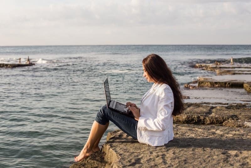 Fêmea autônomo com o portátil preto na praia foto de stock
