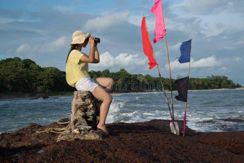 Fêmea bonita asiática que senta-se e que descansa em rochas e que olha através dos binóculos fotografia de stock