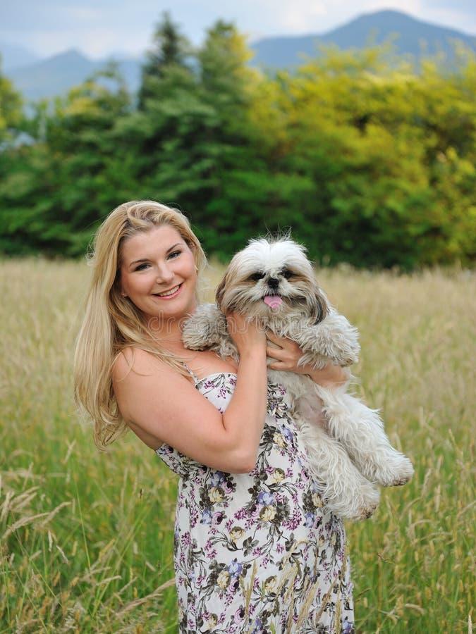Fêmea bonita com o cão pequeno bonito ao ar livre foto de stock