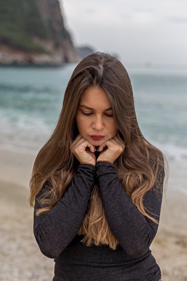 Fêmea bonita com os olhos fechados na praia do inverno foto de stock