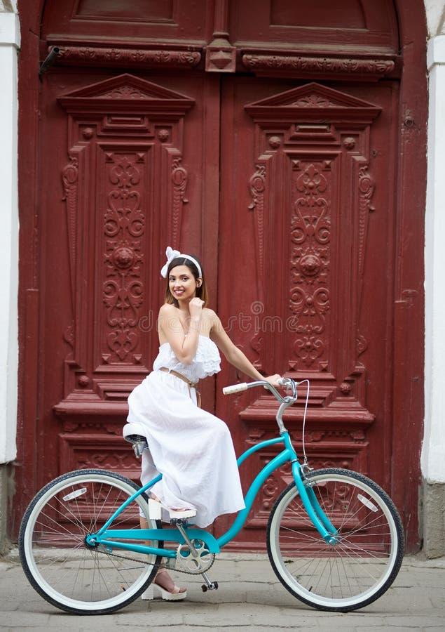 Fêmea bonita no vestido branco que levanta na bicicleta azul do vintage na frente das portas vermelhas velhas bonitas foto de stock