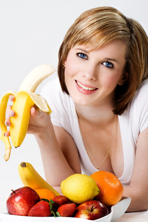 Fêmea bonita nova que come um bananna fotos de stock royalty free