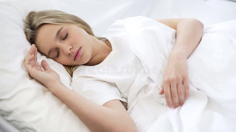Fêmea bonita nova que dorme quietamente na cama, colchão ortopédico confortável fotografia de stock royalty free