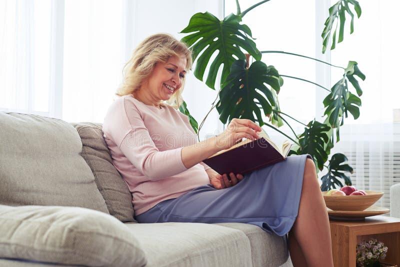 Fêmea bonita que sorri ao girar a página do livro imagens de stock royalty free
