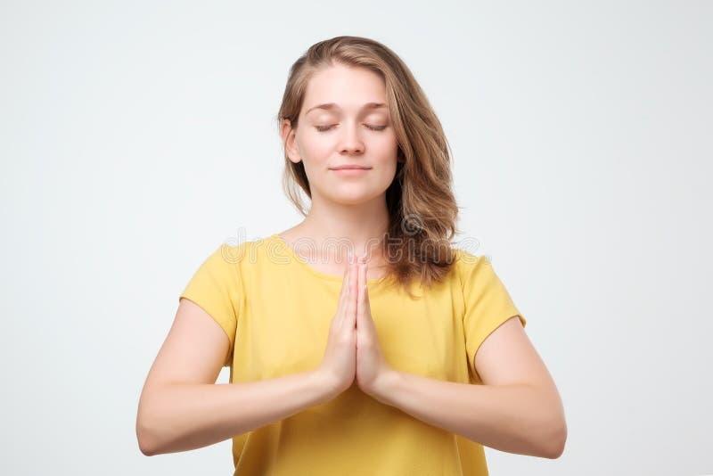 A fêmea calma repousante sente relaxado na camisa amarela, está perto da parede cinzenta, tenta concentrar-se ou ser focalizada imagem de stock royalty free