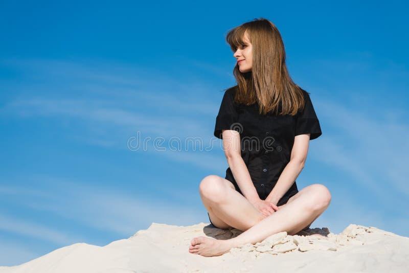 A fêmea caucasiano atrativa senta-se em dunas de areia foto de stock royalty free