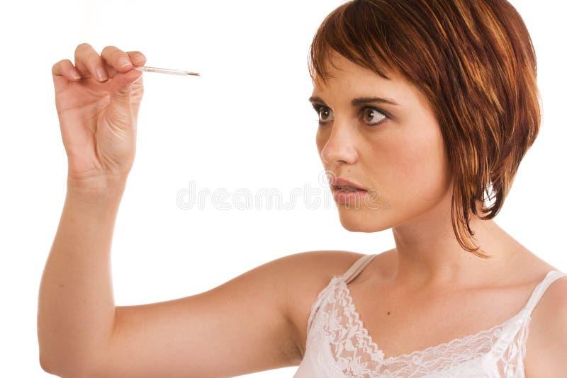 Fêmea caucasiano que verific sua temperatura foto de stock