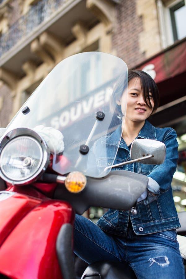 Fêmea chinesa nova no 'trotinette' em Paris imagens de stock