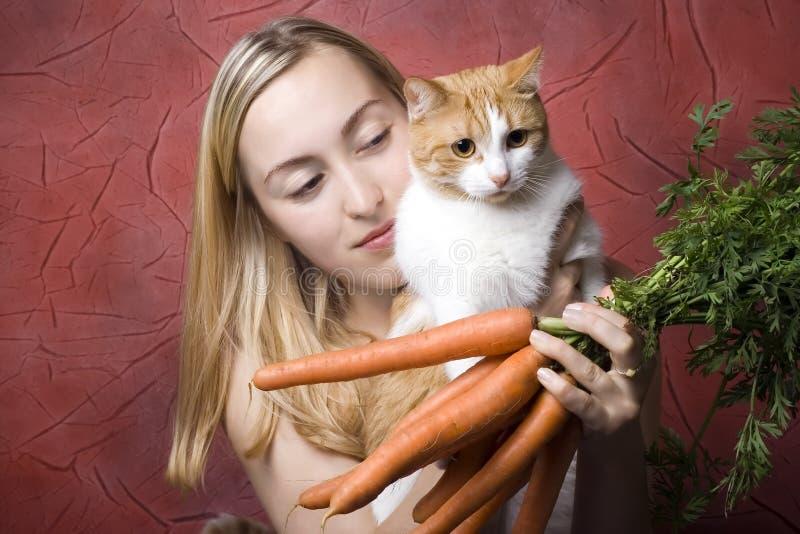 Fêmea com cenouras e gato imagens de stock royalty free