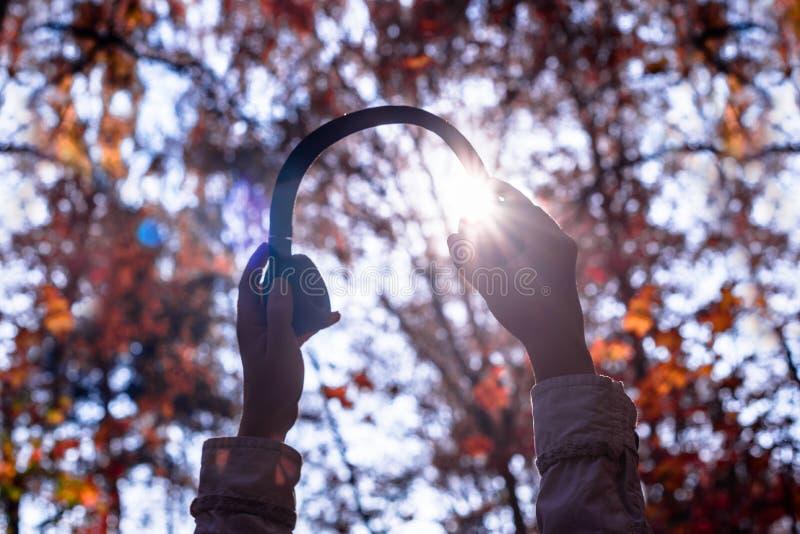 A fêmea com fones de ouvido que anda no parque escuta sons ou música do conceito da floresta do outono Temporada de ver?o indiana fotos de stock