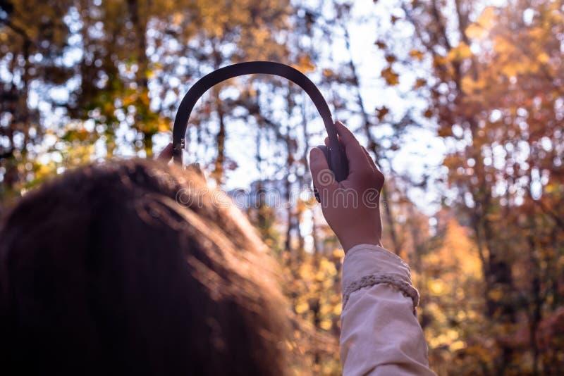 A fêmea com fones de ouvido que anda no parque escuta sons ou música do conceito da floresta do outono Temporada de ver?o indiana fotografia de stock royalty free