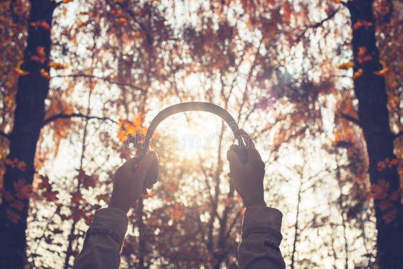 A fêmea com fones de ouvido que anda no parque escuta sons ou música do conceito da floresta do outono Temporada de ver?o indiana foto de stock royalty free