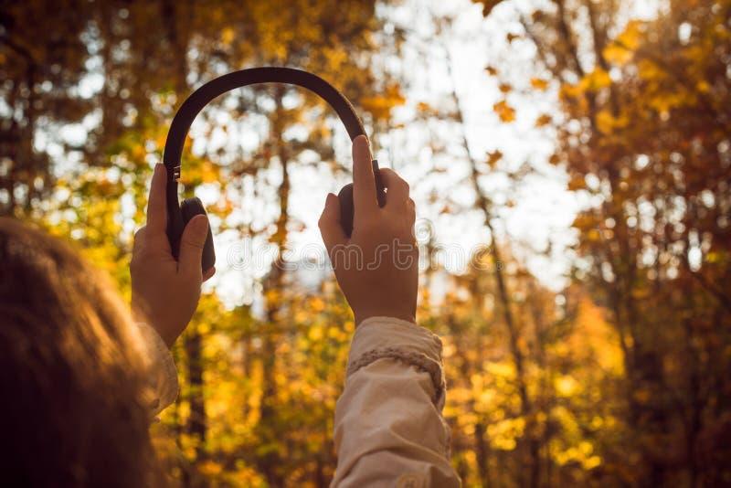 A fêmea com fones de ouvido que anda no parque escuta sons ou música do conceito da floresta do outono Temporada de ver?o indiana imagem de stock