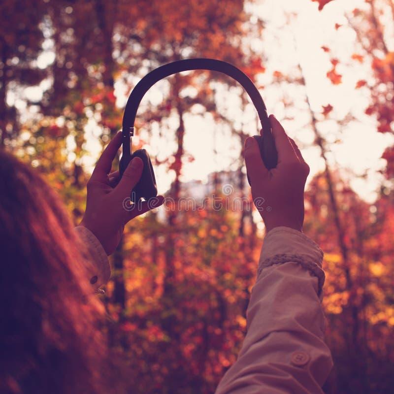 A fêmea com fones de ouvido que anda no parque escuta sons ou música do conceito da floresta do outono Ver?o indiano fotografia de stock royalty free