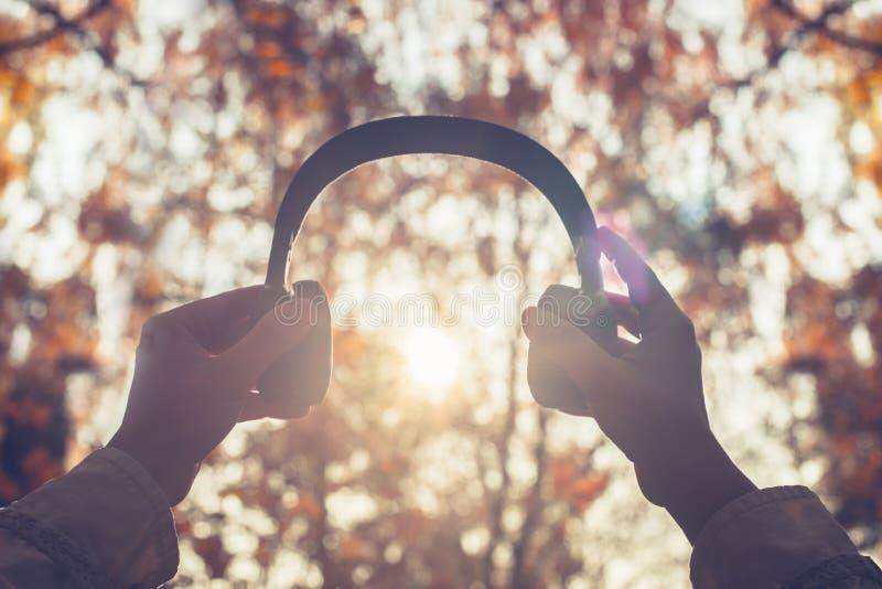 A fêmea com fones de ouvido que anda no parque escuta sons ou música do conceito da floresta do outono Ver?o indiano fotos de stock royalty free
