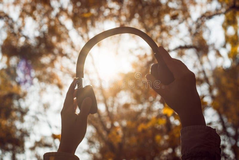A fêmea com fones de ouvido que anda no parque escuta sons ou música do conceito da floresta do outono Ver?o indiano imagem de stock
