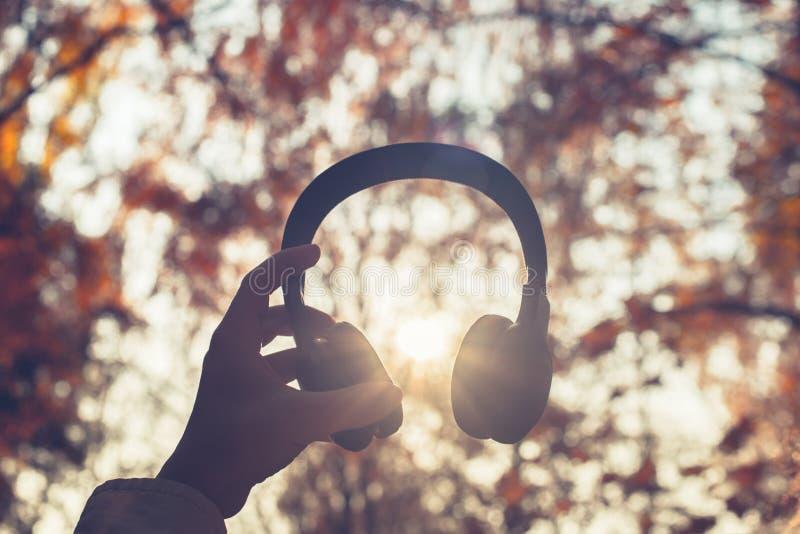 A fêmea com fones de ouvido que anda no parque escuta sons ou música do conceito da floresta do outono Ver?o indiano imagens de stock royalty free