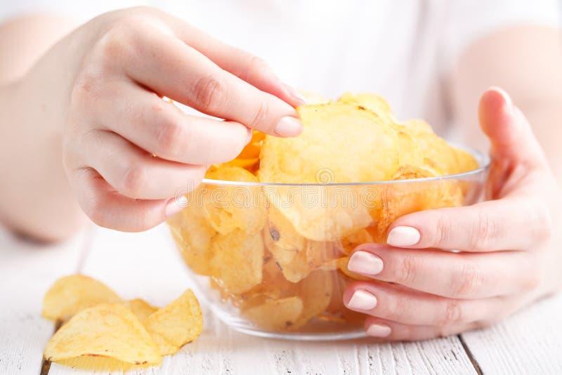 Fêmea com o montão de microplaquetas de batata no prato grande fotos de stock