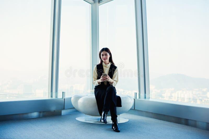 A fêmea com o telefone de pilha nas mãos está sentando-se no interior luxuoso com projeto moderno imagens de stock royalty free