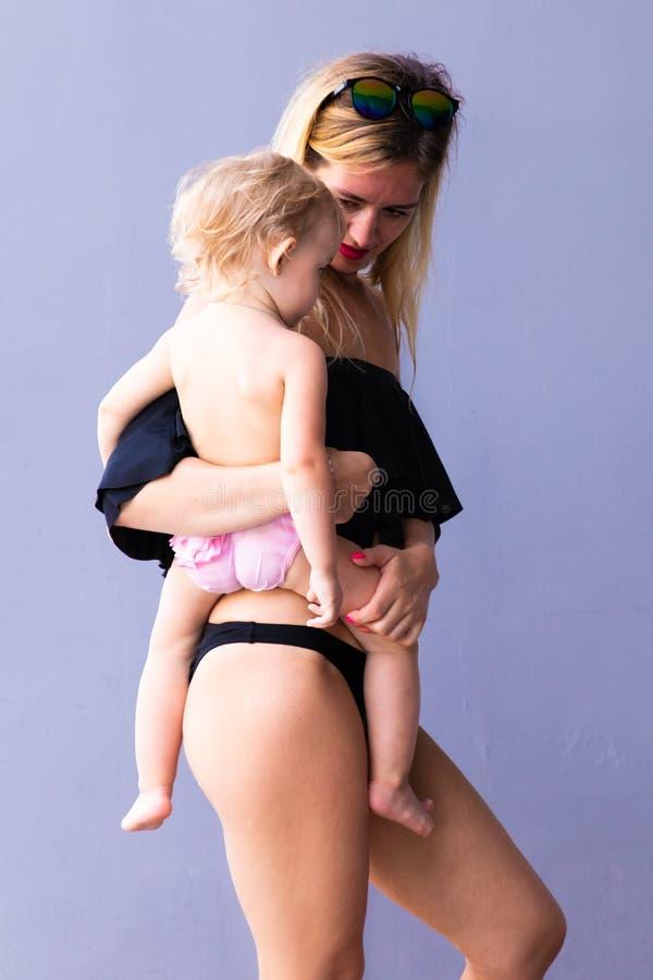 Fêmea com um bebê em seus braços a olhar de sobrancelhas franzidas e em risos contra um fundo azul fotografia de stock
