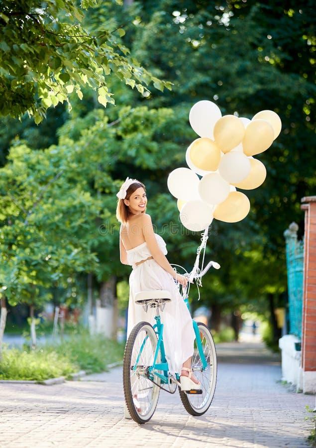 Fêmea consideravelmente nova no vestido branco que guarda ballons e que olha para trás ao montar a bicicleta azul em um parque imagens de stock
